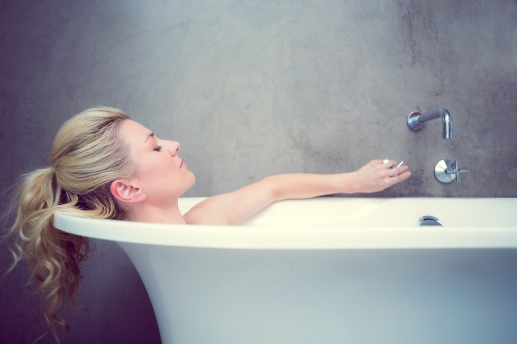 Serene blonde lying in the bath at home in the bathroom